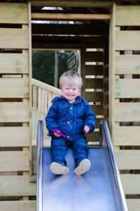 Happy sliding on the mini slide at Audley End Miniature Railway